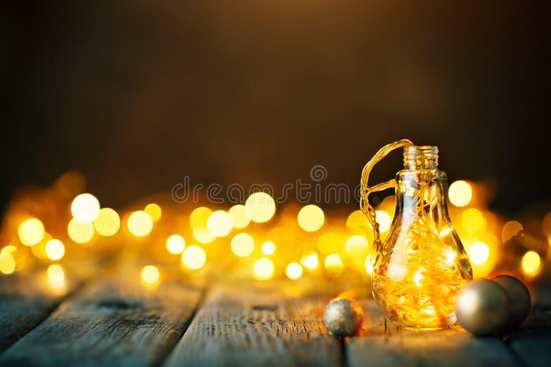 Feliz Navidad y Feliz Año Nuevo Guirnalda de la Navidad en un tarro de cristal en una tabla de madera Foco selectivo fotos de archivo