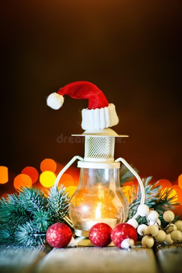 Feliz Navidad y Feliz Año Nuevo Juguetes de la vela y de la Navidad en una tabla de madera en el fondo de una guirnalda Bokeh imagen de archivo libre de regalías