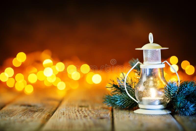 Feliz Navidad y Feliz Año Nuevo Juguetes de la vela y de la Navidad en una tabla de madera en el fondo de una guirnalda Bokeh fotografía de archivo libre de regalías