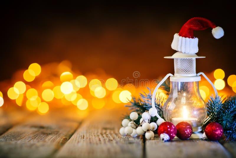 Feliz Navidad y Feliz Año Nuevo Juguetes de la vela y de la Navidad en una tabla de madera en el fondo de una guirnalda Bokeh imágenes de archivo libres de regalías