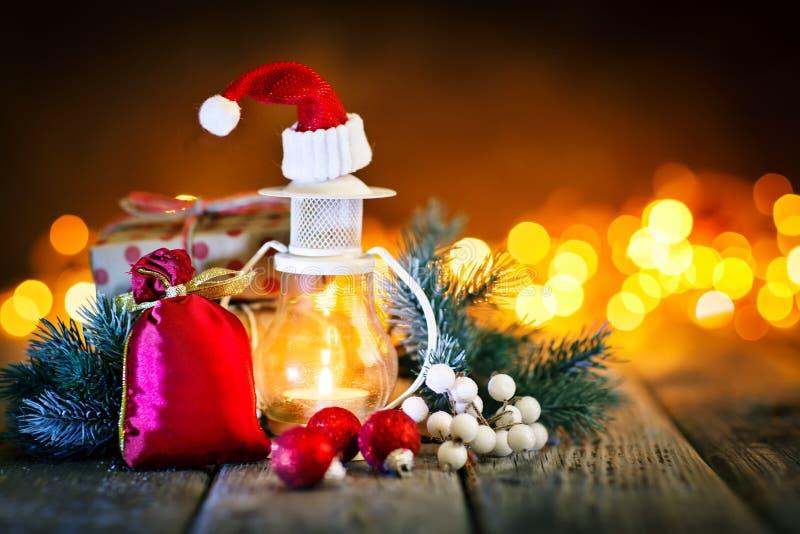 Feliz Navidad y Feliz Año Nuevo Juguetes de la vela y de la Navidad en una tabla de madera en el fondo de una guirnalda Bokeh imagen de archivo