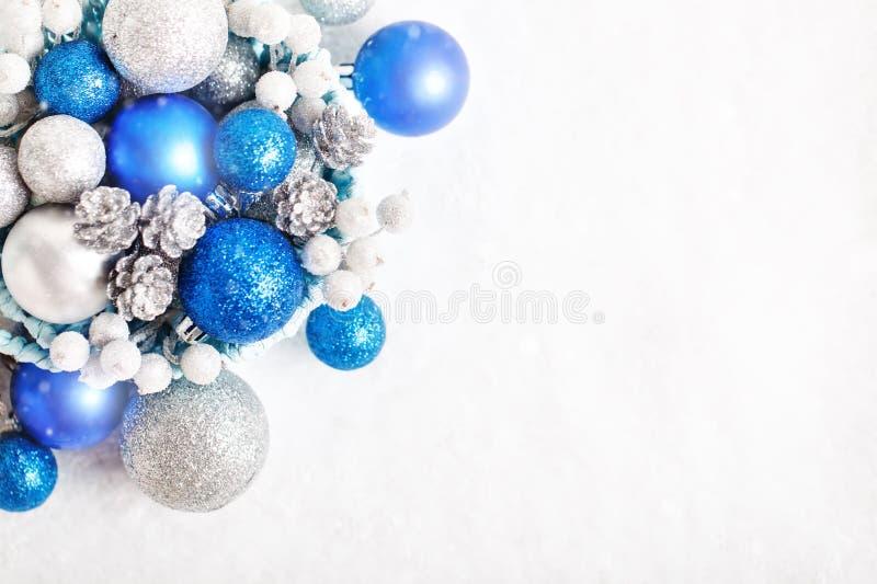 Feliz Navidad y Feliz Año Nuevo La Navidad azul y de plata juega en un fondo ligero Foco selectivo Visión superior foto de archivo
