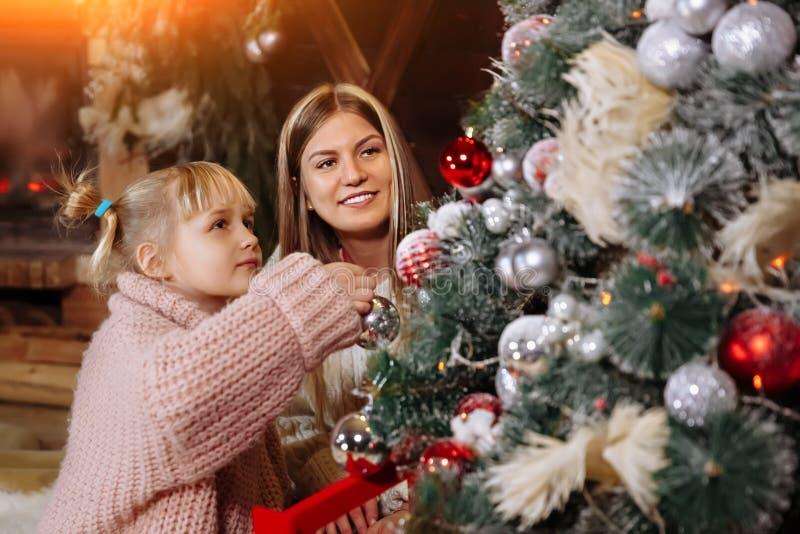 Feliz Navidad y Feliz Año Nuevo La mamá y la hija adornan el árbol de navidad dentro Cierre de amor de la familia para arriba imágenes de archivo libres de regalías