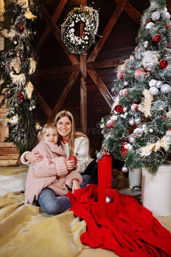 Feliz Navidad y Feliz Año Nuevo La mamá y la hija adornan el árbol de navidad dentro Cierre de amor de la familia para arriba fotos de archivo libres de regalías