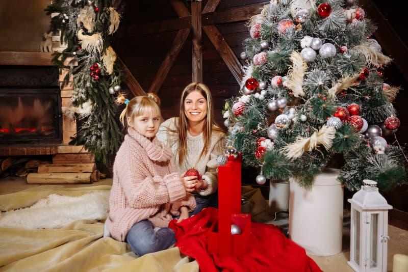 Feliz Navidad y Feliz Año Nuevo La mamá y la hija adornan el árbol de navidad dentro Cierre de amor de la familia para arriba imagen de archivo libre de regalías