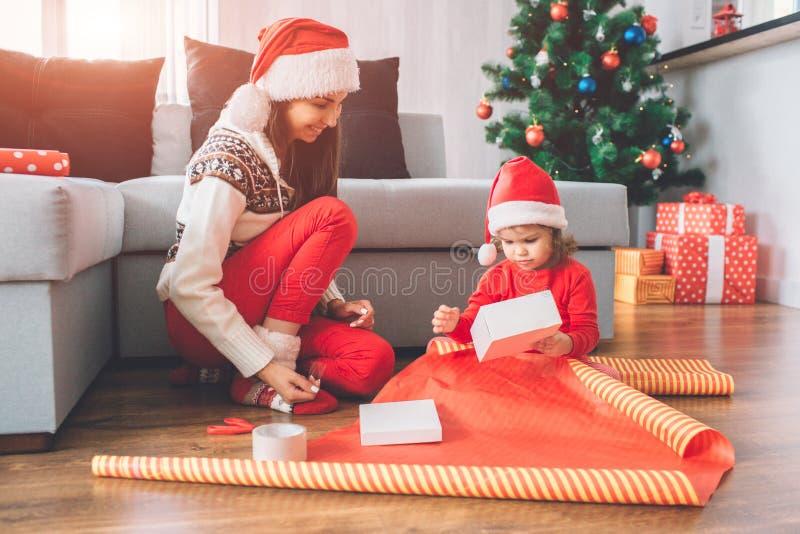 Feliz Navidad y Feliz Año Nuevo La pequeña muchacha se sienta en piso Ella sostiene la caja blanca en manos El niño está intentan fotografía de archivo libre de regalías