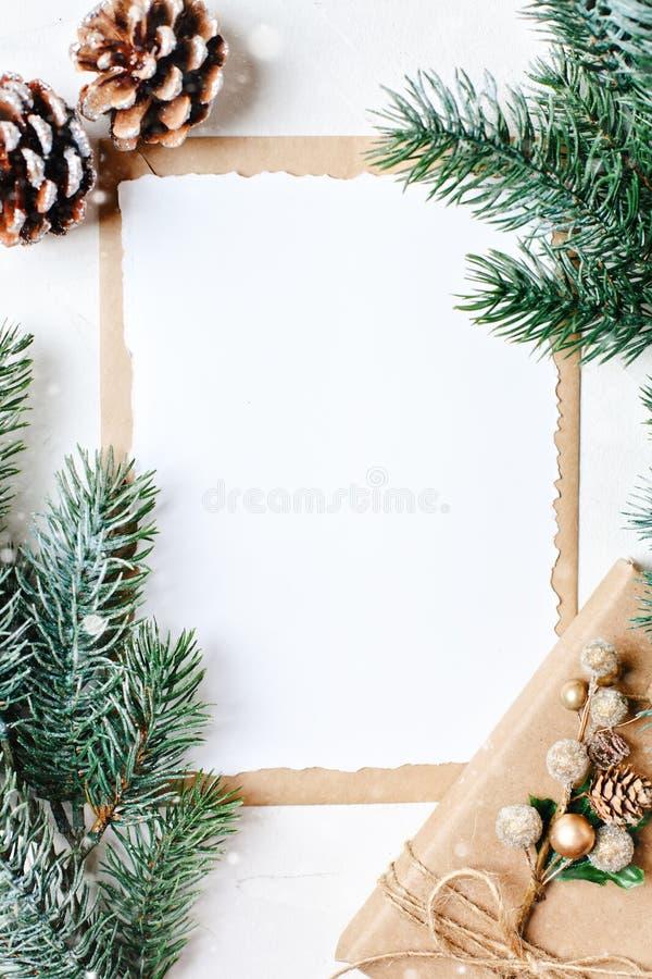 Feliz Navidad y Feliz Año Nuevo Maqueta con la postal y las ramas de un árbol de navidad en el fondo blanco foto de archivo