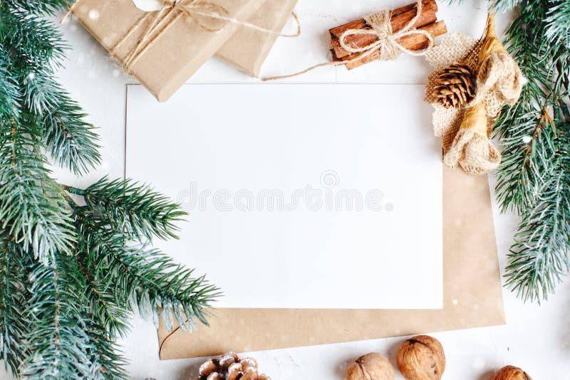 Feliz Navidad y Feliz Año Nuevo Maqueta con la postal y las ramas de un árbol de navidad en el fondo blanco foto de archivo libre de regalías