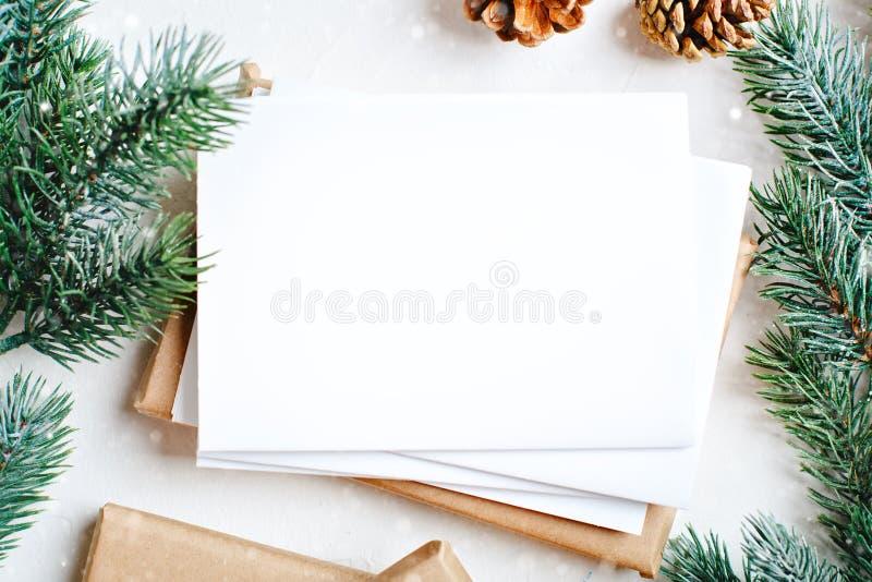 Feliz Navidad y Feliz Año Nuevo Maqueta con la postal y las ramas de un árbol de navidad en el fondo blanco imagenes de archivo