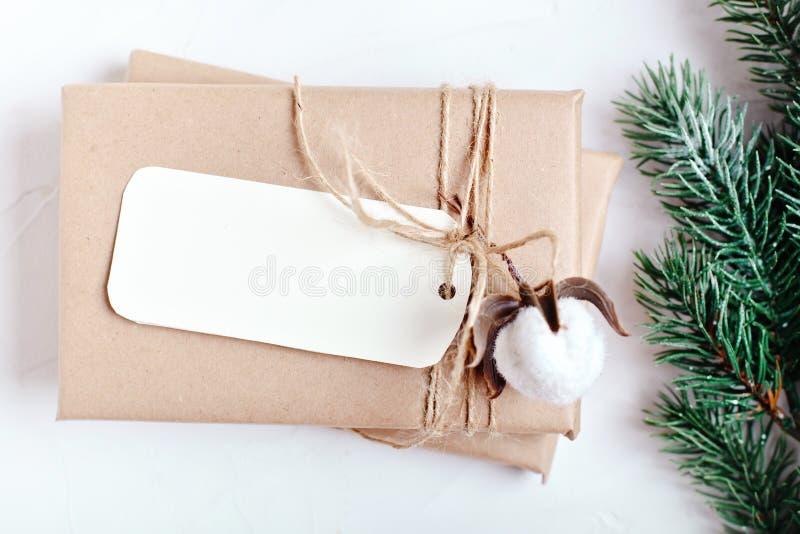 Feliz Navidad y Feliz Año Nuevo Maqueta con la postal y las ramas de un árbol de navidad en el fondo blanco fotos de archivo
