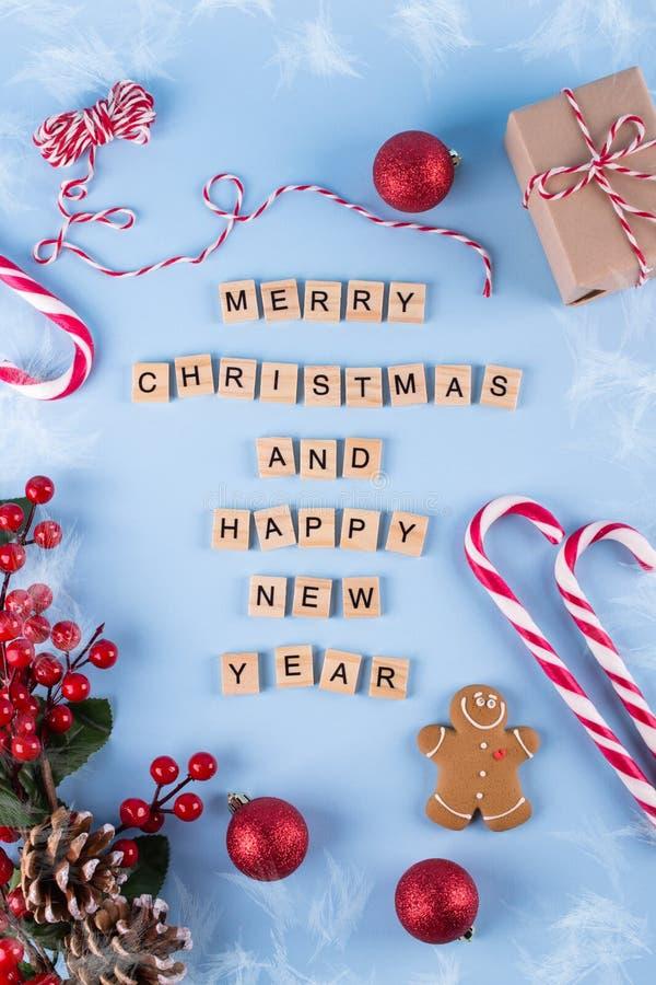 Feliz Navidad y Feliz Año Nuevo Palabras de letras de madera en fondo del invierno y decoraciones azules de la Navidad Plantilla, fotografía de archivo libre de regalías