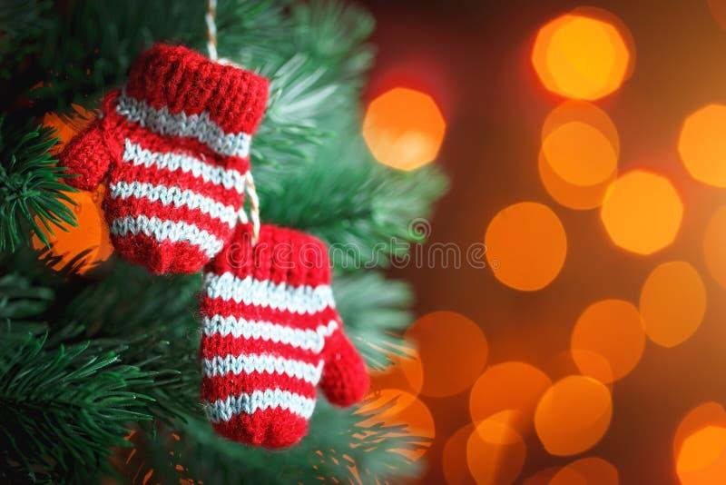 Feliz Navidad y Feliz Año Nuevo Pequeñas manoplas hechas punto en el árbol de navidad Fondo con el espacio de la copia imágenes de archivo libres de regalías