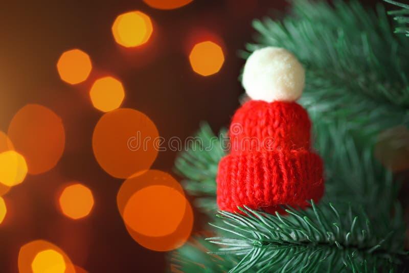 Feliz Navidad y Feliz Año Nuevo Poco sombrero hecho punto en el árbol de navidad Fondo con el espacio de la copia imágenes de archivo libres de regalías