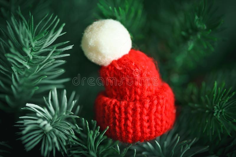 Feliz Navidad y Feliz Año Nuevo Poco sombrero hecho punto en el árbol de navidad Fondo con el espacio de la copia imagen de archivo