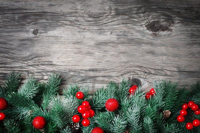 Feliz Navidad y Feliz Año Nuevo Ramas de la picea y juguetes de la Navidad en un fondo de madera fondo con la copia imagen de archivo