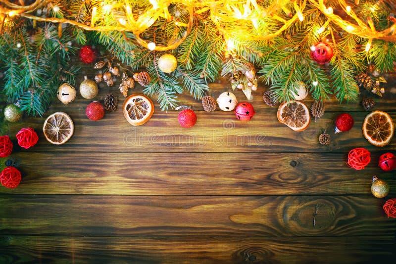 Feliz Navidad y Feliz Año Nuevo Ramas de la picea y juguetes de la Navidad en un fondo de madera fondo con la copia imagenes de archivo