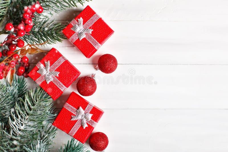 Feliz Navidad y Feliz Año Nuevo Regalos y ramas del abeto en una tabla de madera blanca Foco selectivo Navidad fotos de archivo