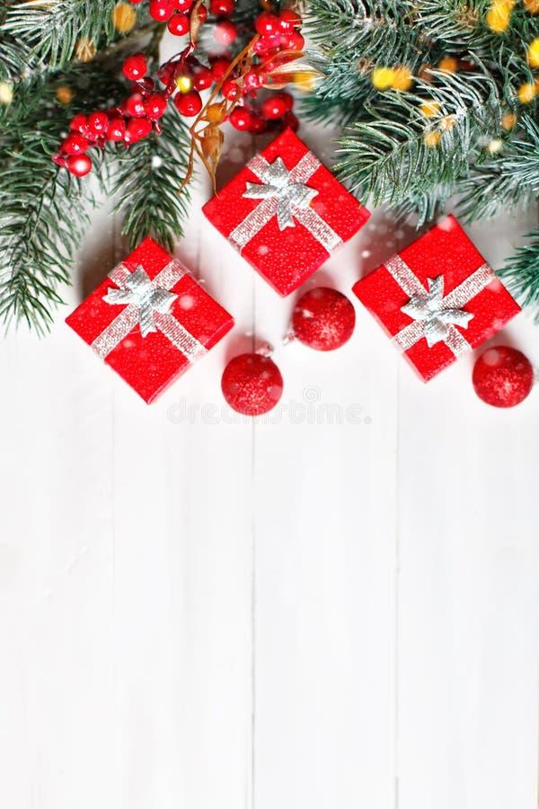 Feliz Navidad y Feliz Año Nuevo Regalos y ramas del abeto en una tabla de madera blanca Foco selectivo Navidad fotografía de archivo libre de regalías