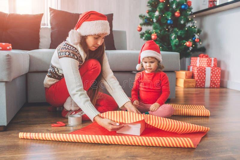 Feliz Navidad y Feliz Año Nuevo Seriousand concentró a la mujer sienta y cubre la caja con el papel La pequeña muchacha mira foto de archivo libre de regalías