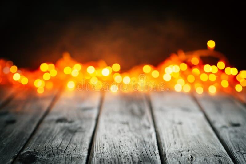 Feliz Navidad y Feliz Año Nuevo Tabla de madera en fondo de las luces de la Navidad Bokeh Foco selectivo Fondo con fotografía de archivo libre de regalías