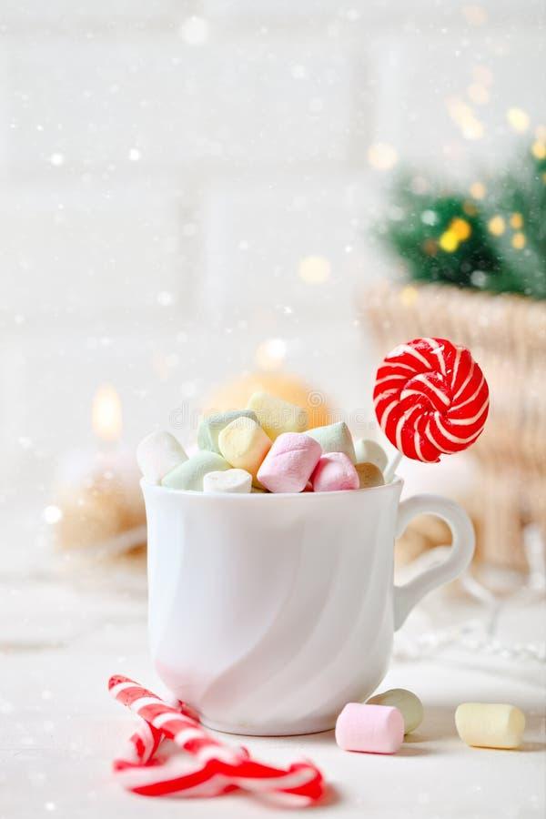 Feliz Navidad y Feliz Año Nuevo Taza de cacao y de melcochas en un fondo ligero Fondo con el espacio de la copia imagenes de archivo