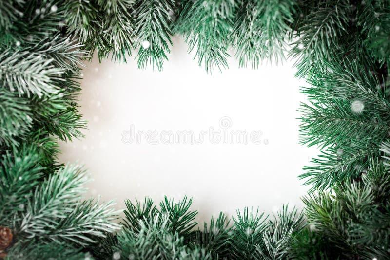 Feliz Navidad y Feliz Año Nuevo Un marco de las ramas del abeto en un fondo blanco Fondo con el espacio de la copia fotos de archivo libres de regalías