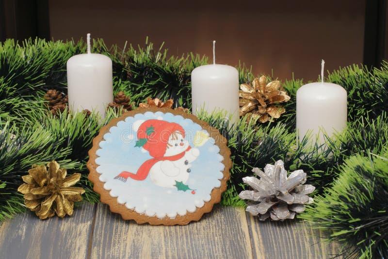 Feliz Navidad y Feliz Año Nuevo Velas de la cera, conos, un muñeco de nieve con una campana, malla verde contra la perspectiva de imágenes de archivo libres de regalías