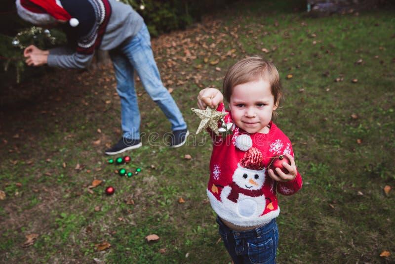 Feliz Navidad y buenas fiestas Heps de la niña su padre que adorna el árbol de navidad al aire libre en la yarda del BEF de la ca imágenes de archivo libres de regalías