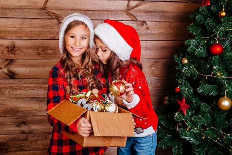 Feliz Navidad y buenas fiestas Las pequeñas hermanas lindas adornan el árbol en casa imágenes de archivo libres de regalías