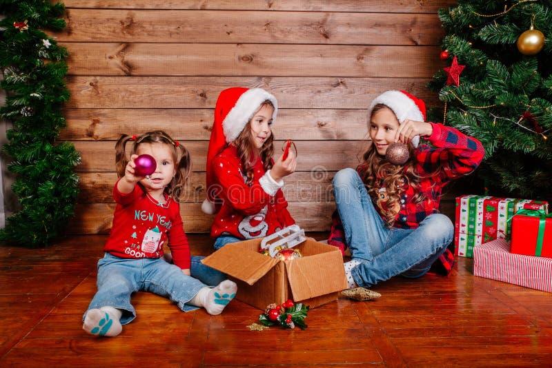 Feliz Navidad y buenas fiestas Las pequeñas hermanas lindas adornan el árbol en casa imagen de archivo libre de regalías