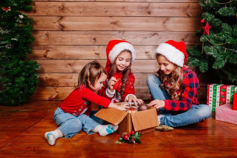 Feliz Navidad y buenas fiestas Las pequeñas hermanas lindas adornan el árbol en casa fotografía de archivo libre de regalías