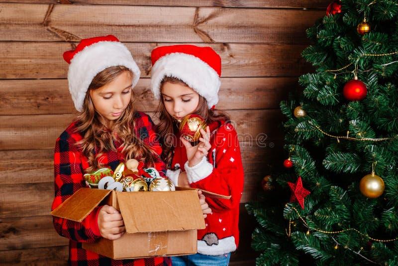 Feliz Navidad y buenas fiestas Las pequeñas hermanas lindas adornan el árbol en casa foto de archivo