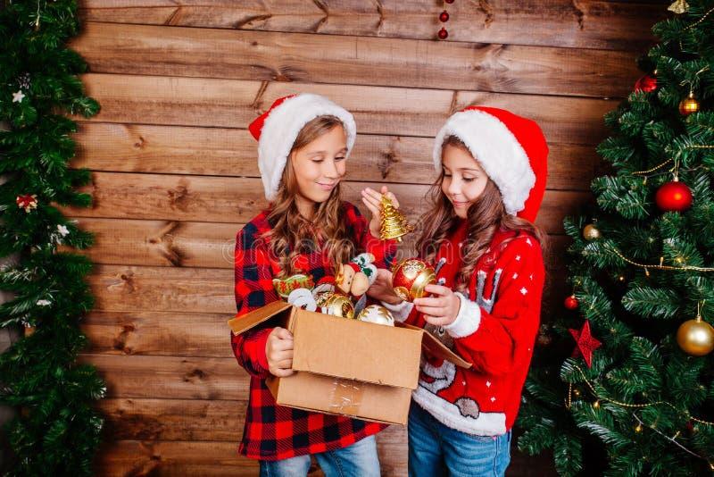 Feliz Navidad y buenas fiestas Las pequeñas hermanas lindas adornan el árbol en casa imagenes de archivo