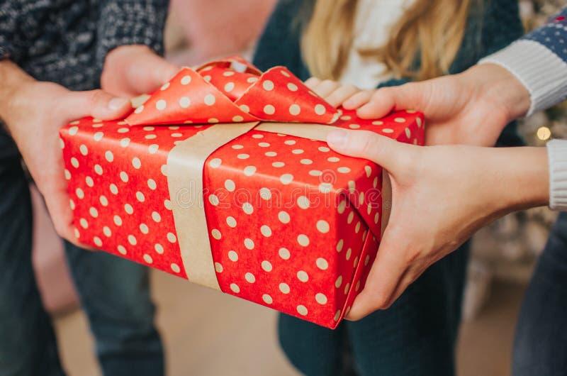 Feliz Navidad y buenas fiestas madre alegre, padre y su muchacha linda de la hija intercambiando los regalos Padre y foto de archivo