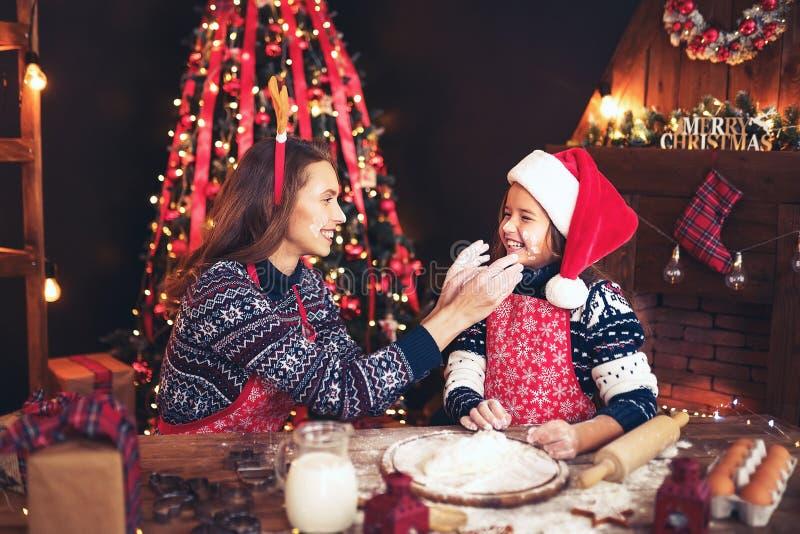 Feliz Navidad y buenas fiestas Madre e hija que cocinan las galletas de la Navidad foto de archivo libre de regalías