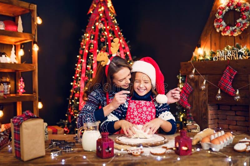Feliz Navidad y buenas fiestas Madre e hija que cocinan las galletas de la Navidad foto de archivo