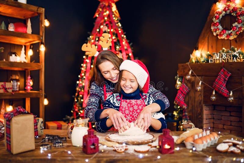 Feliz Navidad y buenas fiestas Madre e hija que cocinan las galletas de la Navidad fotografía de archivo