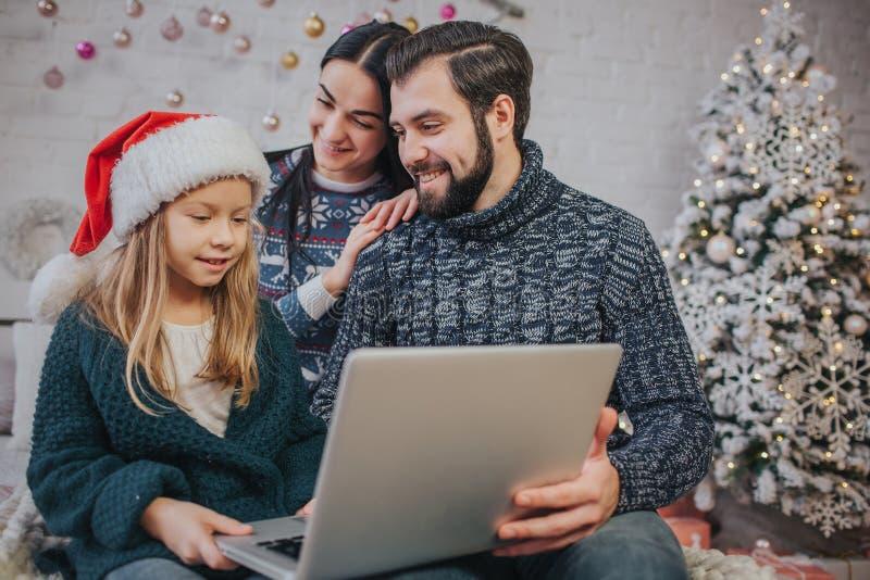 Feliz Navidad y buenas fiestas mamá alegre, papá y su muchacha linda de la hija para utilizar un ordenador portátil Padre y peque fotos de archivo libres de regalías