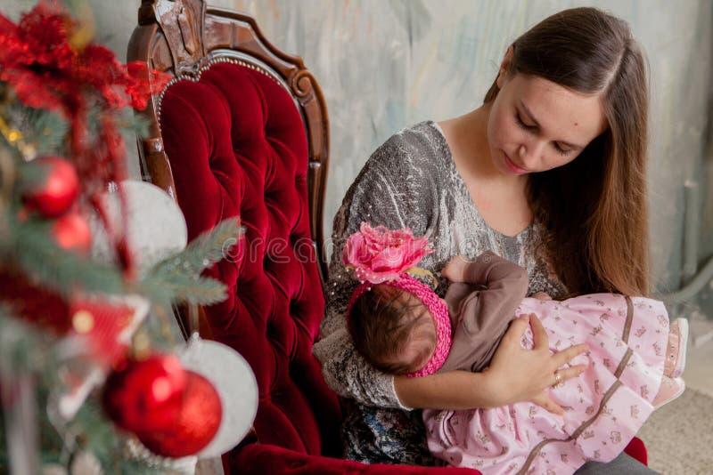 Feliz Navidad y buenas fiestas mamá joven bonita que leen un libro a su hija linda cerca del árbol de navidad dentro foto de archivo