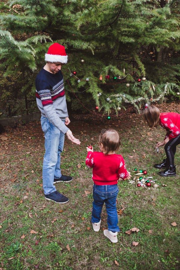 Feliz Navidad y buenas fiestas Padre en sombrero rojo de la Navidad y dos las hijas en suéteres rojos que adornan al ou del árbol foto de archivo