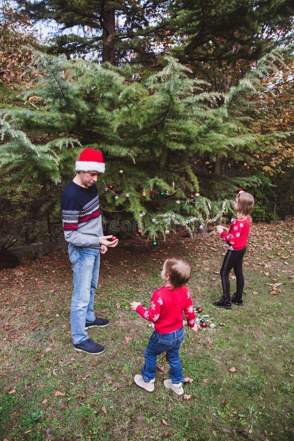 Feliz Navidad y buenas fiestas Padre en sombrero rojo de la Navidad y dos las hijas en suéteres rojos que adornan al ou del árbol imagen de archivo libre de regalías