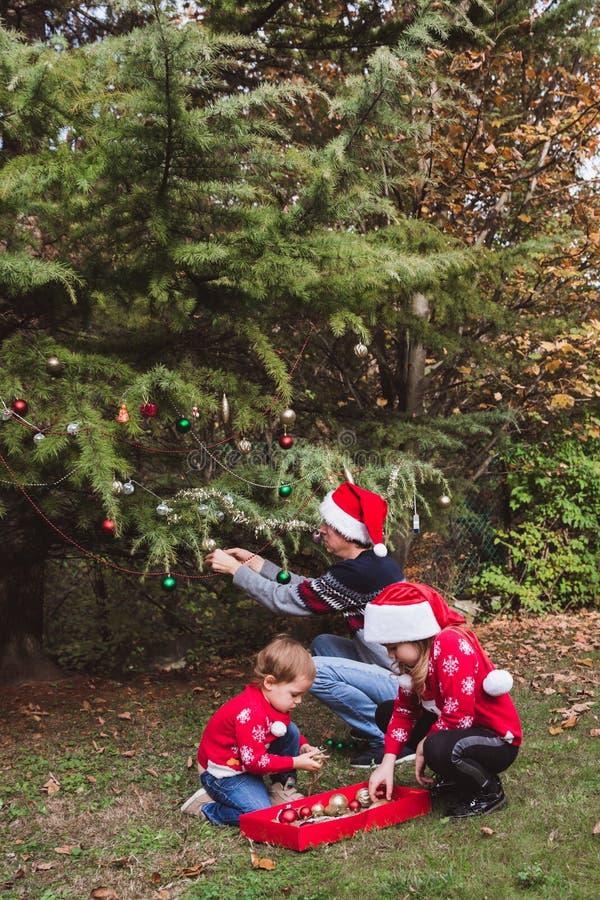 Feliz Navidad y buenas fiestas Padre en sombrero rojo de la Navidad y dos las hijas en suéteres rojos que adornan al ou del árbol fotografía de archivo
