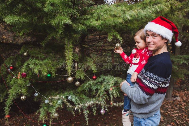 Feliz Navidad y buenas fiestas Padre en sombrero rojo y la hija de la Navidad en suéter rojo que adornan el árbol de navidad al a foto de archivo