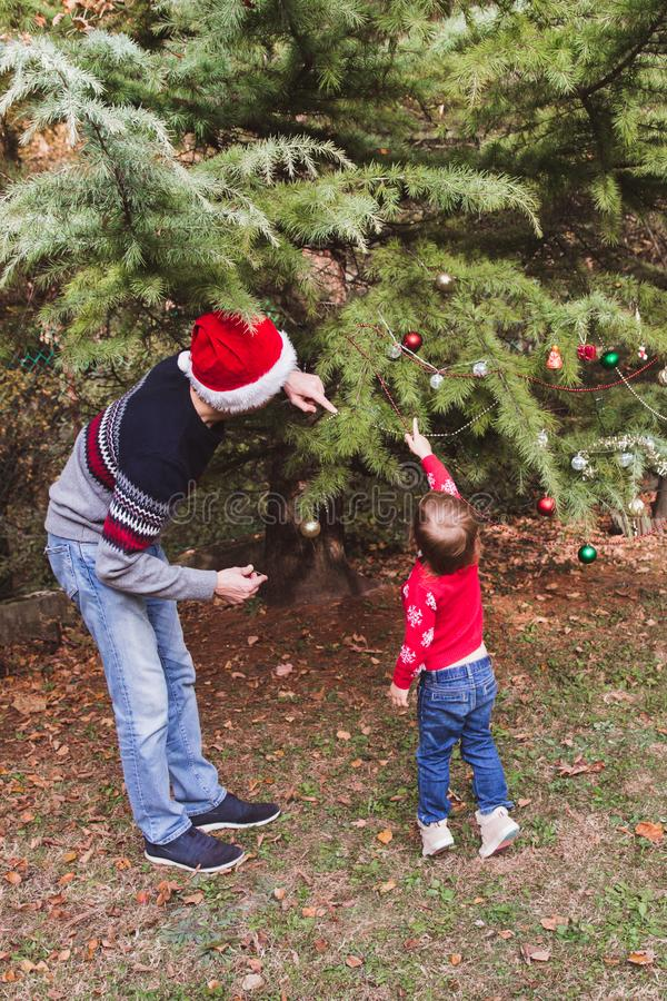 Feliz Navidad y buenas fiestas Padre en sombrero rojo y la hija de la Navidad en suéter rojo que adornan el árbol de navidad al a imagen de archivo