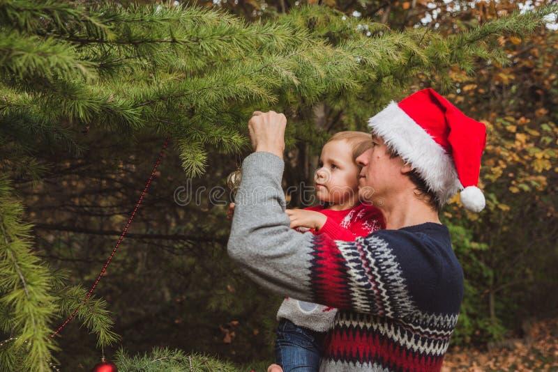 Feliz Navidad y buenas fiestas Padre en sombrero rojo y la hija de la Navidad en suéter rojo que adornan la Navidad imágenes de archivo libres de regalías