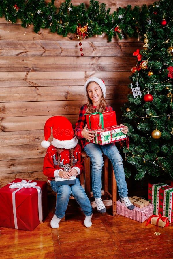 Feliz Navidad y día de fiesta feliz Dos muchachas lindas del pequeño niño con las actuales cajas de regalo cerca del árbol interi imagen de archivo libre de regalías