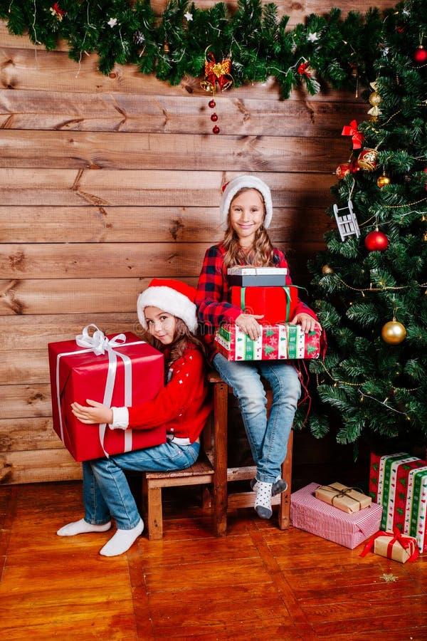 Feliz Navidad y día de fiesta feliz Dos muchachas lindas del pequeño niño con las actuales cajas de regalo cerca del árbol interi foto de archivo