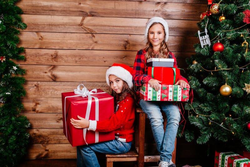 Feliz Navidad y día de fiesta feliz Dos muchachas lindas del pequeño niño con las actuales cajas de regalo cerca del árbol interi imagenes de archivo