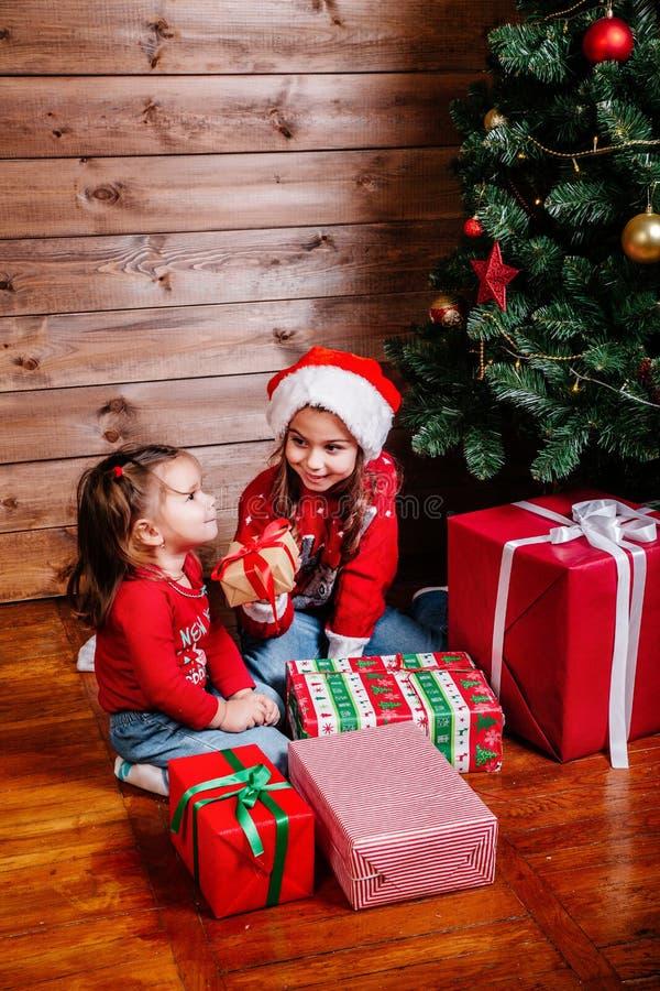 Feliz Navidad y día de fiesta feliz Dos muchachas lindas del pequeño niño con las actuales cajas de regalo cerca del árbol interi fotografía de archivo libre de regalías