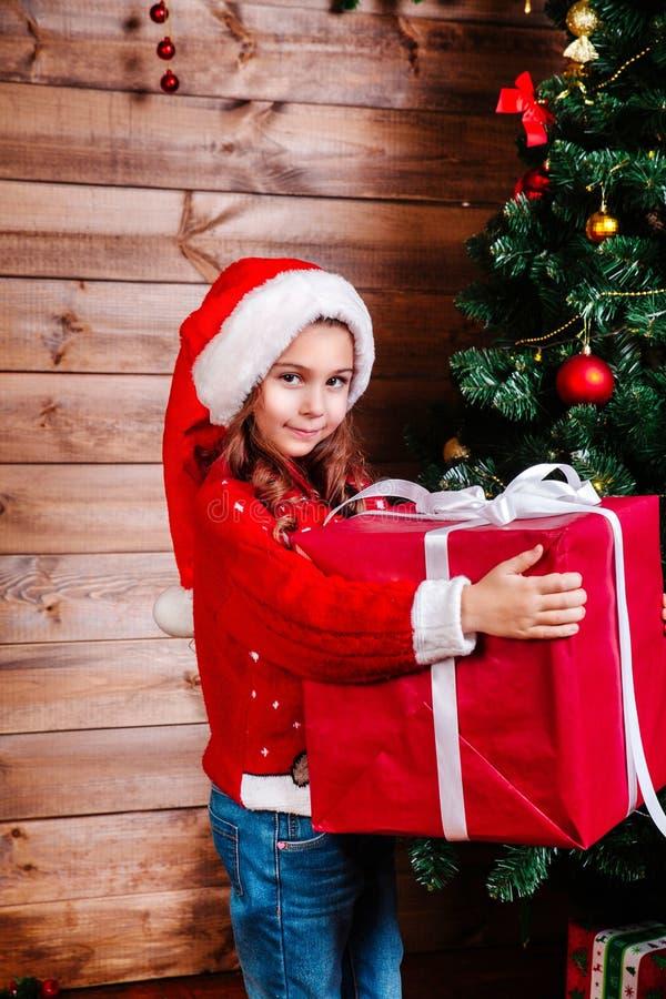 Feliz Navidad y día de fiesta feliz Muchacha linda del pequeño niño con la actual caja de regalo roja grande cerca del árbol inte imagen de archivo